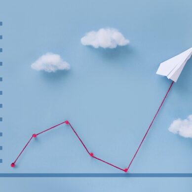 Conceptual origami paper plane pulling business finance growth chart line flying upwards on blue sky background.