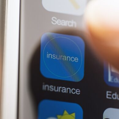 Hand touching insurance app icon on touchscreen